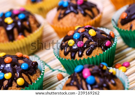 Muffin with chocolate glaze and smarties - stock photo