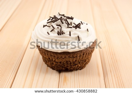 Muffin with cream and chocolate crumbs on top of it sitting on bright wooden table