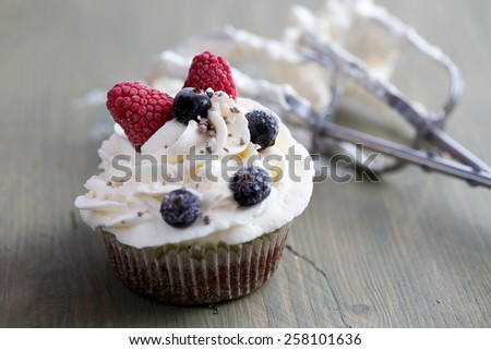 Muffin with whipped cream and frozen berries - stock photo