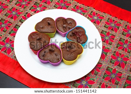 Muffins. Chocolate and raspberry heart shape muffins on festive table. Copy space composition - stock photo