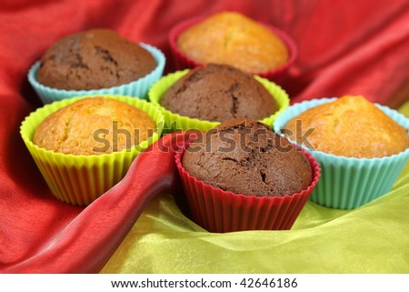 Muffins in colorful silicon moulds on red and green silk - stock photo