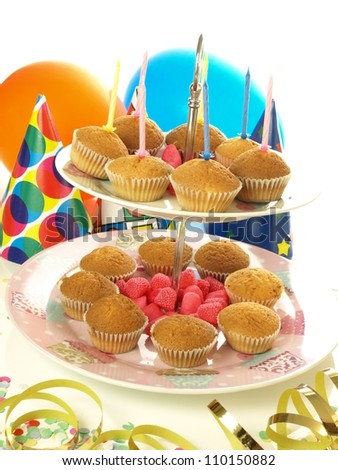 Muffins with birthday candles on white background - stock photo