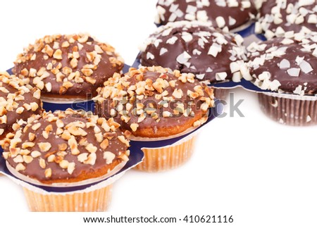 Muffins with chocolate and nuts on white background. - stock photo