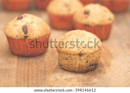 Muffins with chocolate on a wooden table in a shallow depth of field. Homemade pastries in instagram style.