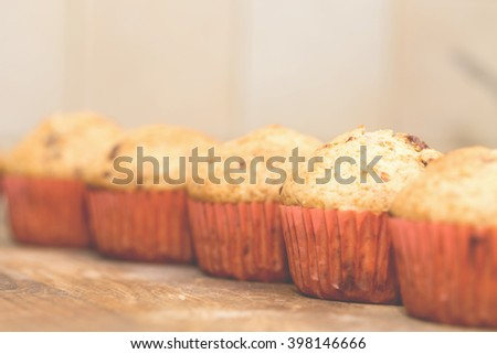 Muffins with chocolate on a wooden table in a shallow depth of field. Homemade pastries in instagram style. - stock photo
