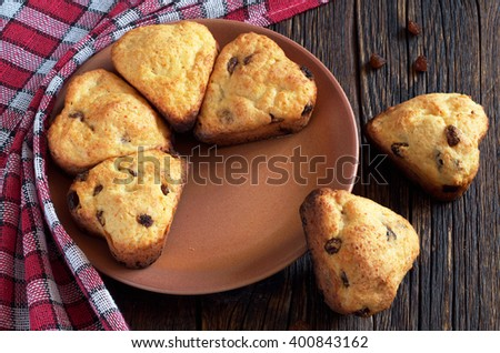 Muffins with raisins in shape of hearts on rustic wooden table - stock photo