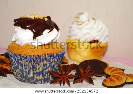 muffins with whipped cream and chocolate sauce and sweet cakes - stock photo