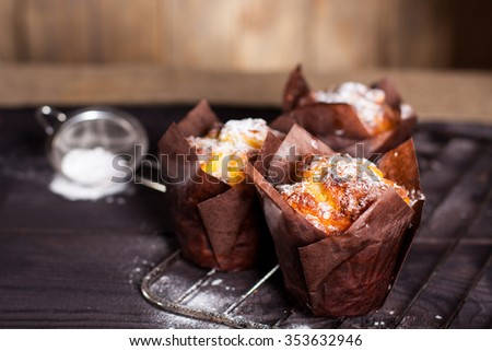 Muffins with white powdered sugar on wooden background.