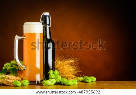 Mug and Bottle of Wheat Beer with Hops and Wheat brewing ingredients. Copy space area