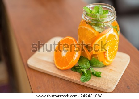 Mug delicious refreshing drink of orange fruit with mint , infused water - stock photo