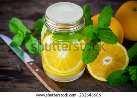 Mug delicious refreshing drink of orange fruit with mint on wooden, infused water - stock photo
