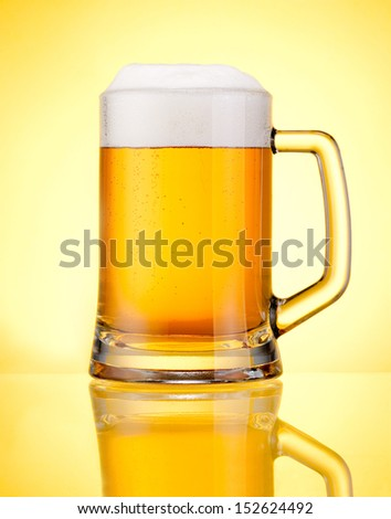 Mug fresh beer with cap of foam isolated over yellow background - stock photo