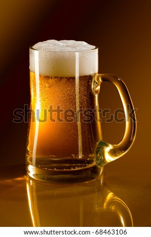 Mug full of beer on a gold background reflected in glass