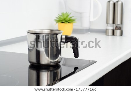 Mug in modern kitchen with induction stove - stock photo