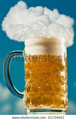 Mug of beer against the cloudy sky - stock photo