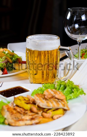 Mug of Beer Amidst Plated Dishes on Restaurant Table - stock photo