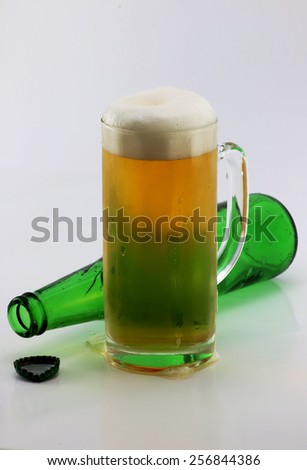 Mug of beer and green beer bottle empty bottle on white background. - stock photo