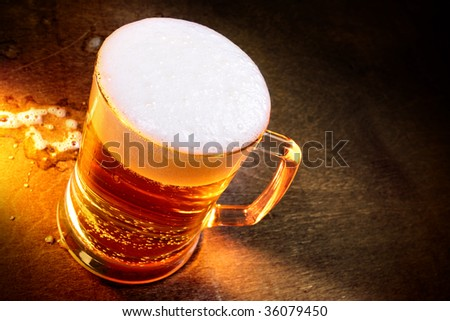 Mug of beer close up on wooden table - stock photo
