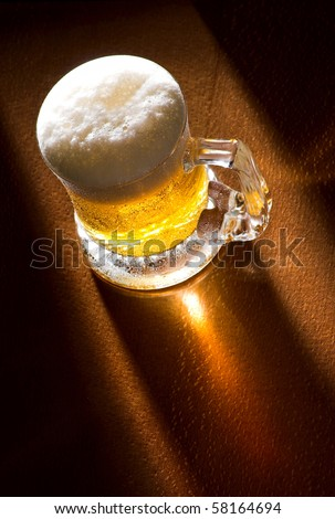 Mug of beer close up on wooden table, spot back-light,  selective focus - stock photo