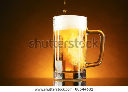 mug of beer on a yellow background - stock photo