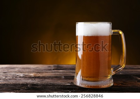Mug of beer on brown wooden background - stock photo