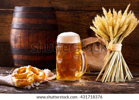 mug of beer with wheat ears and pretzel  on wooden background