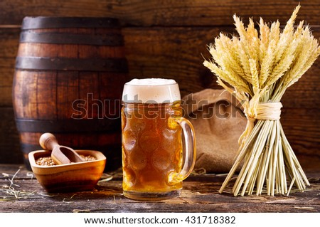 mug of beer with wheat ears on wooden background