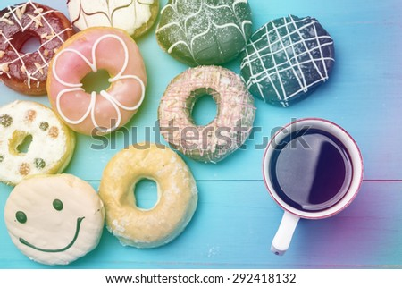 Mug of coffee and donuts on wooden desk vintage - stock photo