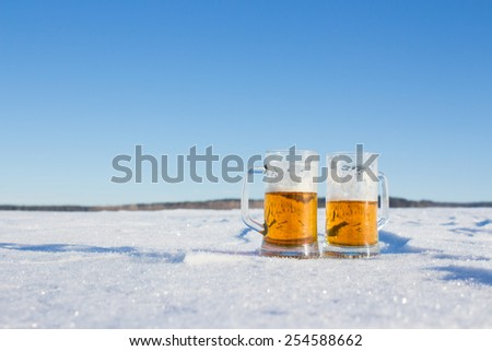 mug of cold beer in the snow