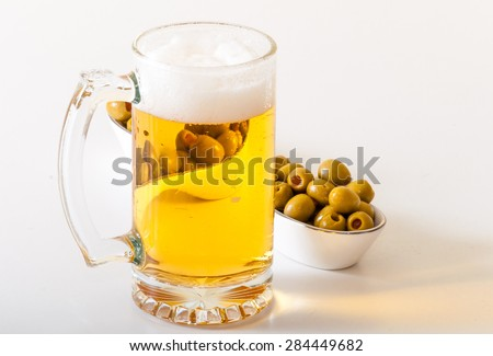 Mug of frothy beer and green olives for snack, a mug of beer beside a dish of green olives. - stock photo