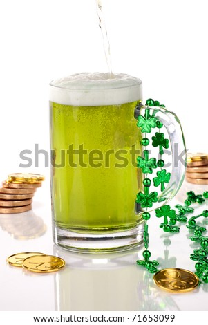 Mug of green beer for St Patrick's Day surrounded with gold coins and shamrock ornament - stock photo