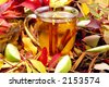 Mug of hot apple cider steeping with cinnamon sticks surrounded by autumn leaves - stock photo