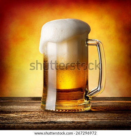 Mug of lager on a wooden table - stock photo