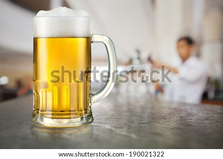 Mug of light beer in pub - stock photo