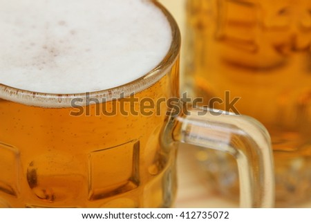 mug of light beer on a table made of wood