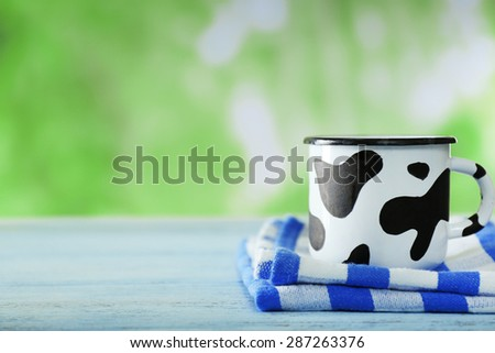 Mug of milk on wooden table, on green nature background - stock photo