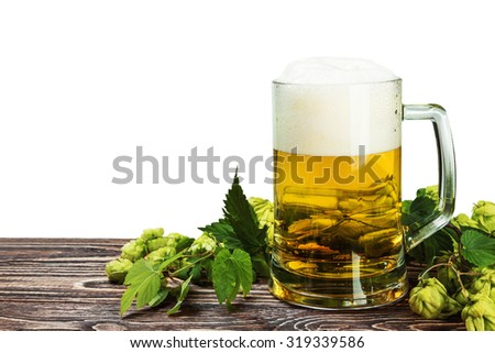 Mug with Beer with hop on wooden table isolated on a white background - stock photo