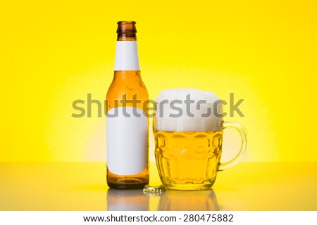 Mug with foamy beer and empty bottle with blank labels on yellow background - stock photo