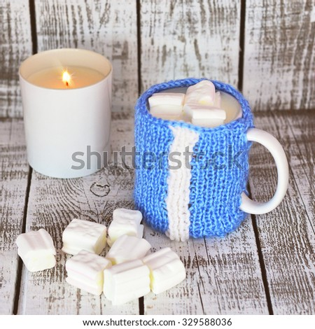 Mug with milk and marshmallow on the white table