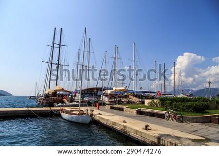 MUGLA, TURKEY - JUNE 1, 2015 : Sailing ships anchored on harbor of Marmaris marina, on blue sky background. - stock photo