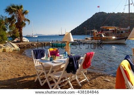 MUGLA, TURKEY - MAY 28, 2016 : View of restaurant with white tables and chairs along Gumusluk beach. - stock photo