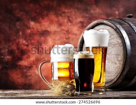 Mugs and glasses with light and dark beer on background wooden barrel