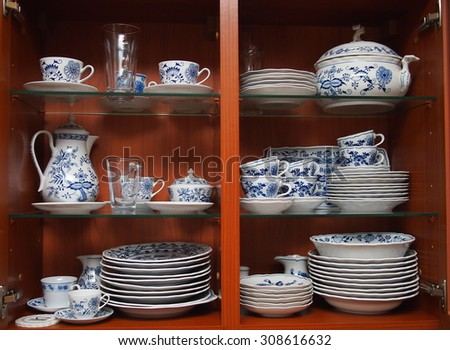 Mugs, cups and plates with blue and white pattern of flowers and onions. All neatly cleaned up in a wooden kitchen cabinet. - stock photo