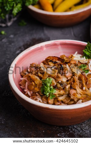 Mujadarra - arabian dish with rice, lentils and onion on dark  background. Ramadan food. Eastern cuisine. Selective focus