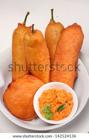 mulaku bajji served in white plate with coconut chutney. Mulaku[chilli] Bajji is a common Snack in South India.It is easy to make and very tasty. - stock photo
