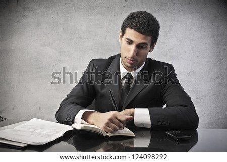 Mulatto businessman writing some papers