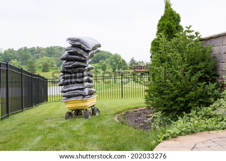 Mulch in bags piled high on a cart in the garden teetering precariously as they wait to be spread over the flowerbeds in a carefully manicured rural garden - stock photo