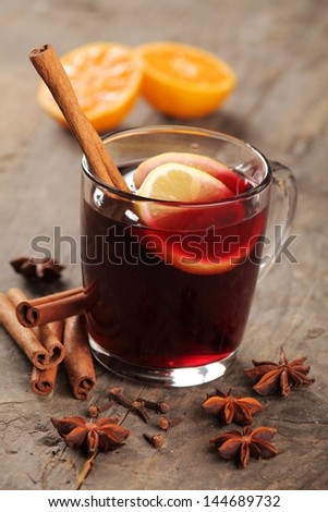 Mulled wine and spices on wooden background. - stock photo