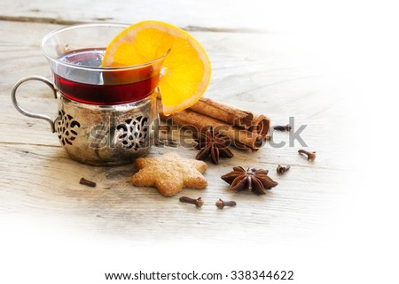 mulled wine, Christmas punch with orange slice and spices like cinnamon, star anise and cloves on rustic light wood, corner background faded to white, copy space - stock photo