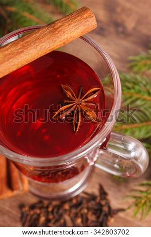 Mulled wine for christmas or winter evening on wooden surface plank, spruce branches and spices, cinnamon anise cloves - stock photo